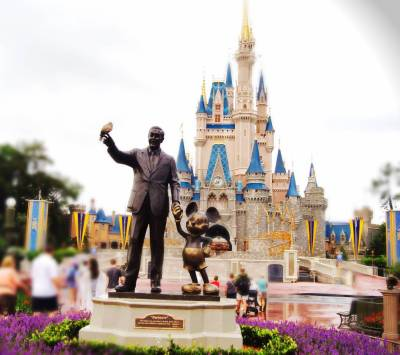 Photo illustrating Walt & Mickey Statue in front of the castle